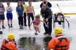 Hole-cut-in-the-ice-of-North-Bar-Lake-Empire-Michigan-as-young-girl-takes-the-polar-bear-plunge