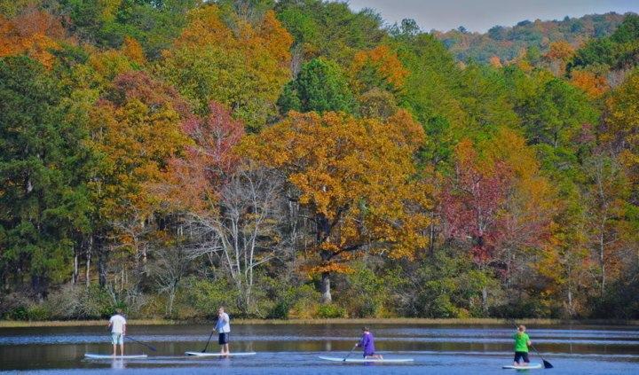 A-group-of-paddleboarders-pass-in-front-of-bright-fall-foliage-at-Oak-Mountain-State-Park-in-Birmingham-Alabama